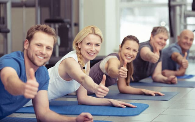 Smiling people on yoga mats